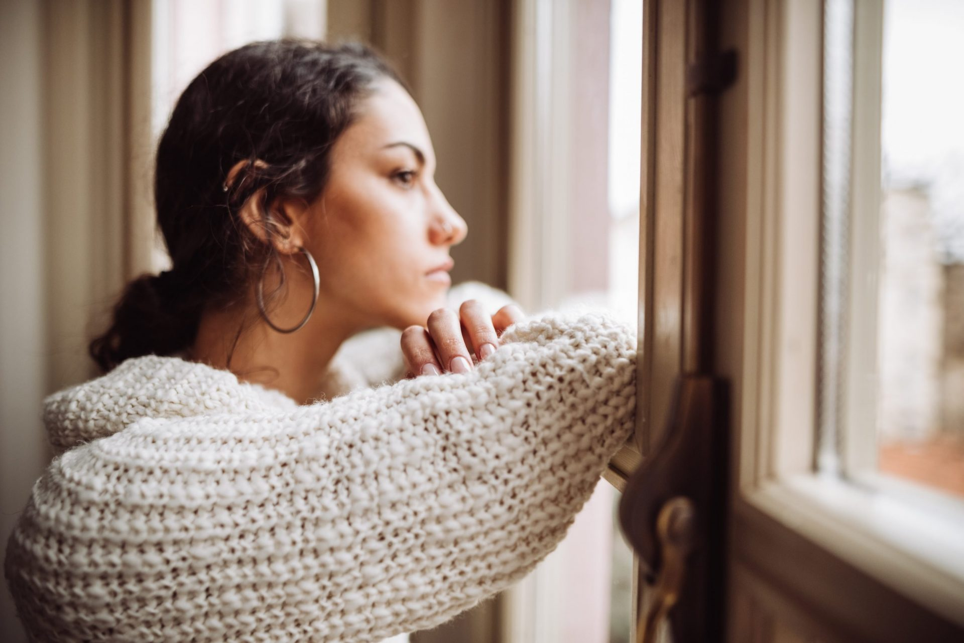 pensive woman in front of the window with young son