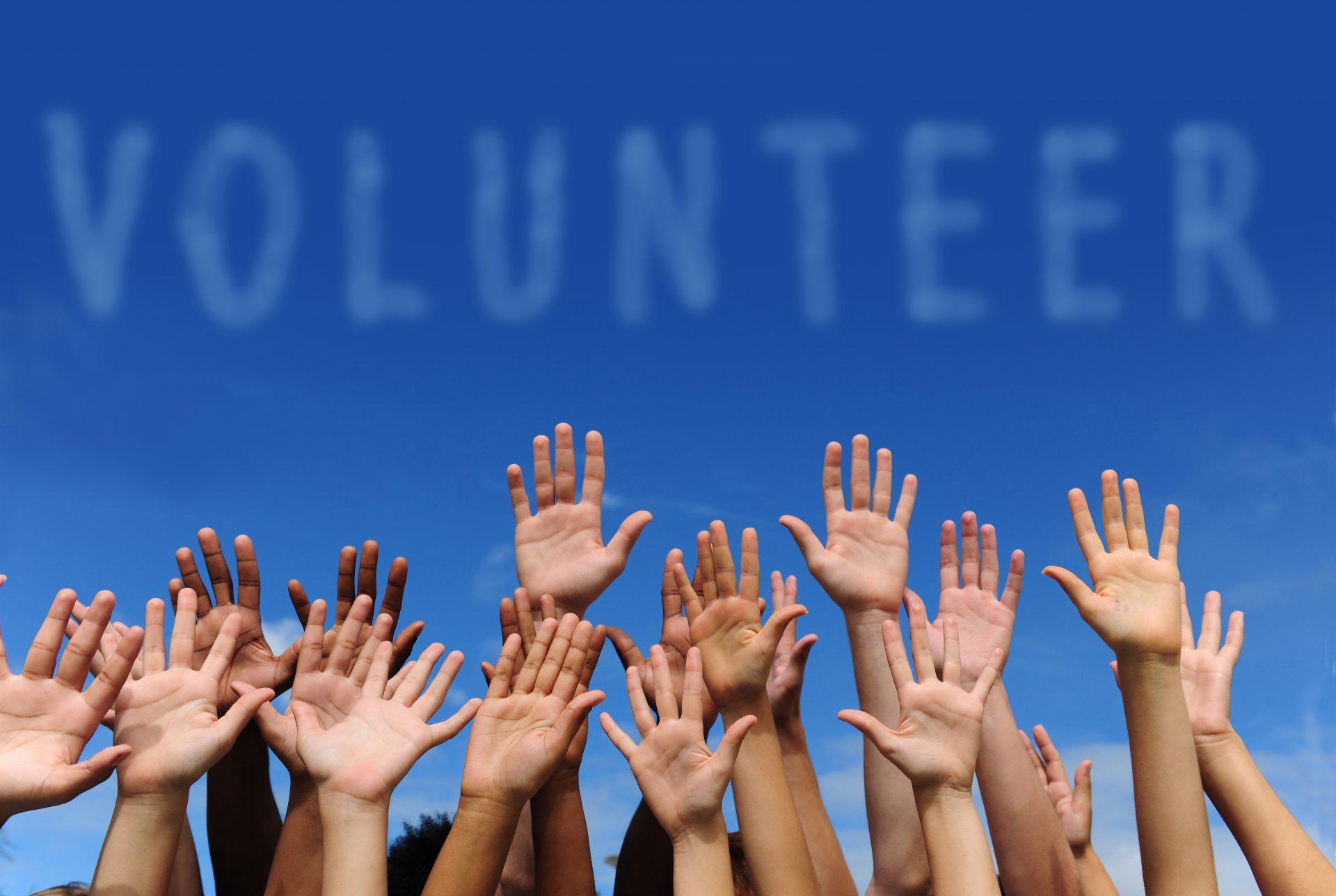Volunteer written in clouds above hands