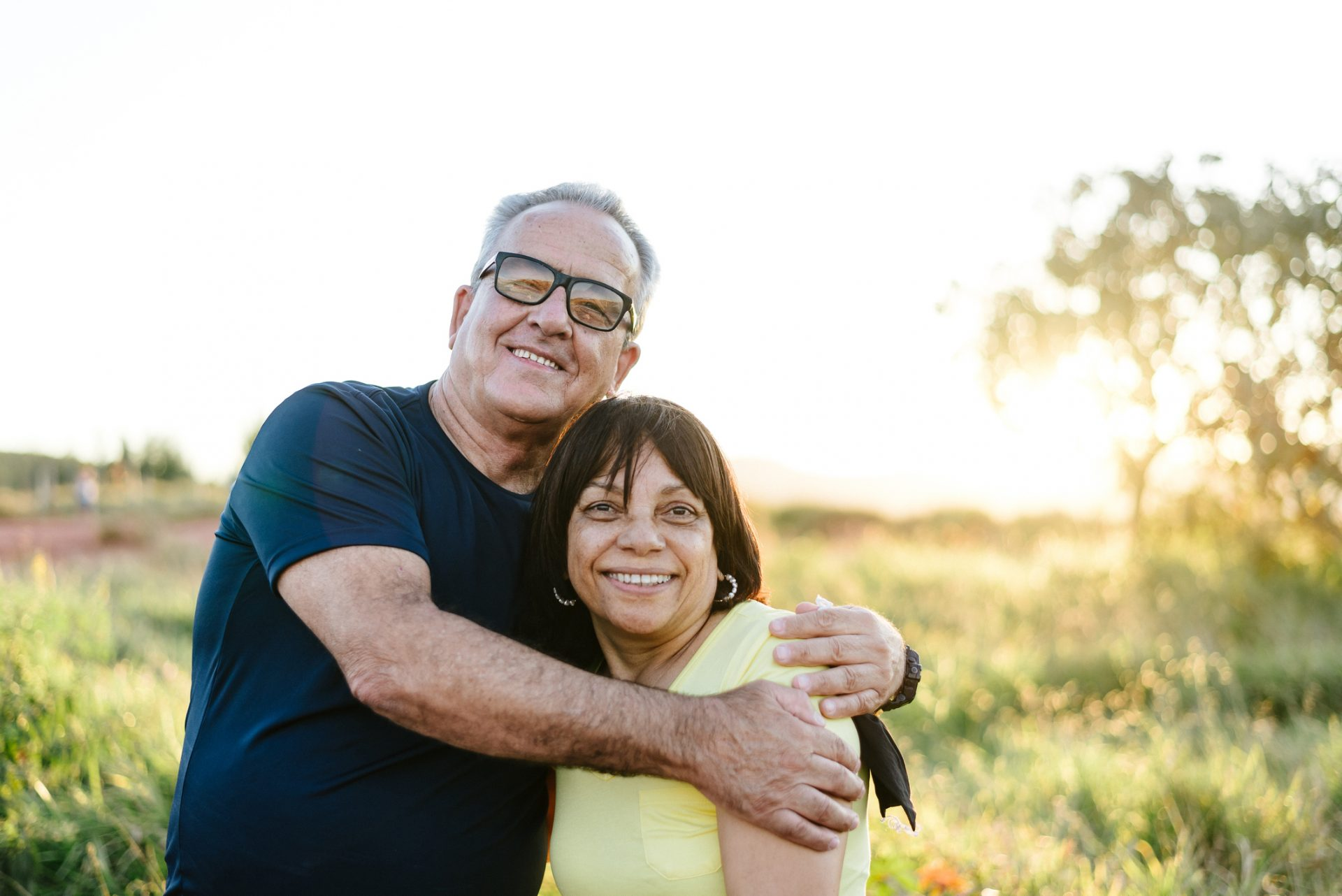 Older couple hugging and smiling outdoors