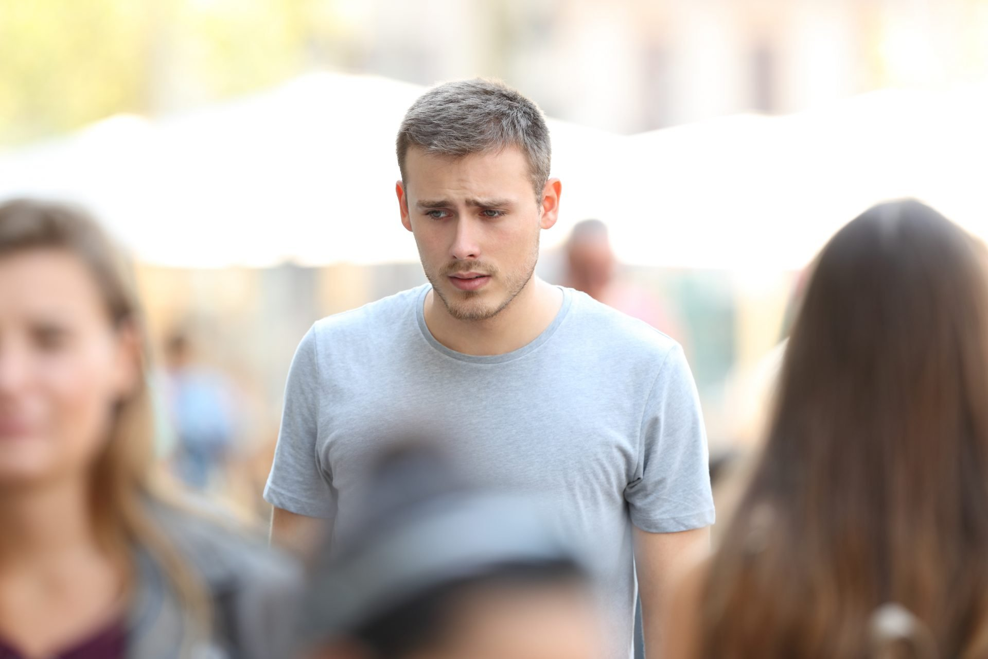 Worried young man amid crowd